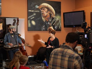 Minister Theresa Oswald makes the announcement after a song by The Crooked Brothers at Le Garage Cafe